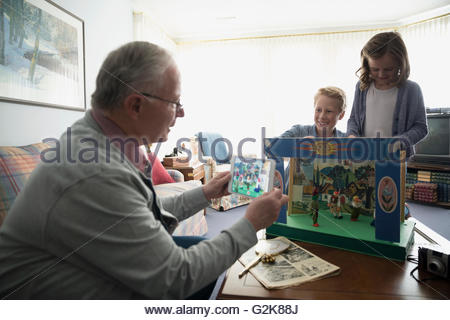 Grandfather with digital tablet photographing grandchildren playing with old puppet set - Stock Photo
