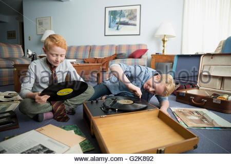 Brothers playing records on old turntable - Stock Photo