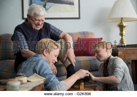 Grandsons polishing shoes for grandfather in living room - Stock Photo