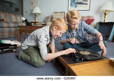 Brothers playing record on old turntable - Stock Photo