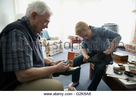 Grandfather teaching grandson how to polish shoes - Stock Photo