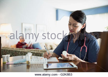 Home caregiver writing notes on prescription medication at dining table - Stock Photo