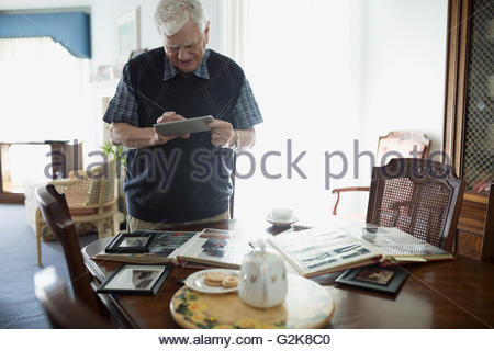 Senior man using digital tablet at dining table with photograph albums - Stock Photo