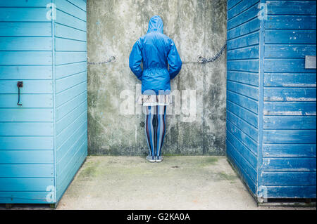 A person is standing with their head against the wall in between two beach huts - Stock Photo