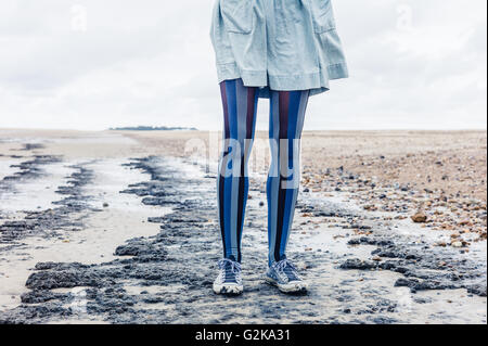 The legs of a young woman as she is standing on the beach with her skirt blowing in the wind - Stock Photo