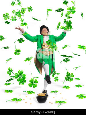 Leprechaun in bright green clothes with a pot full of gold throwing shamrocks up in the air - Stock Photo