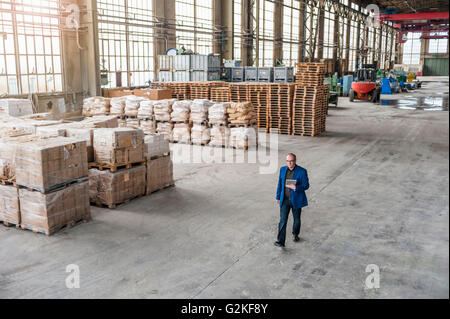 Manager walking through factory hall - Stock Photo
