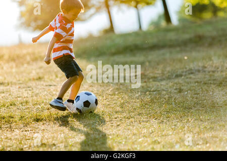 Little boy playing soccer on a meadow - Stock Photo