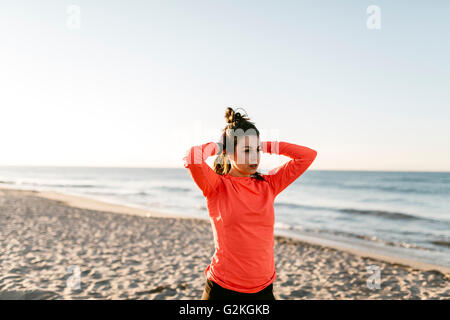 Woman running on the beach early in the morning, hands in hair - Stock Photo