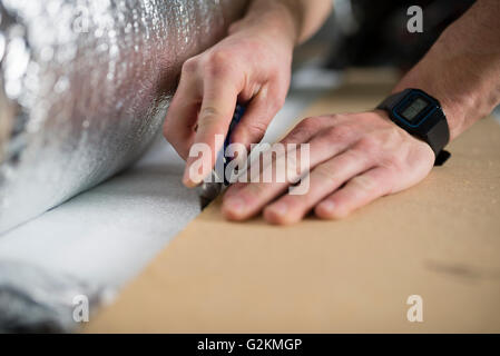 Young man cutting a insulating material for a laminate-flooring - Stock Photo