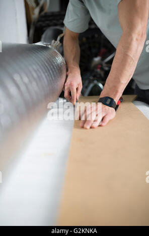 Young man cutting a insulating material for a laminate flooring - Stock Photo
