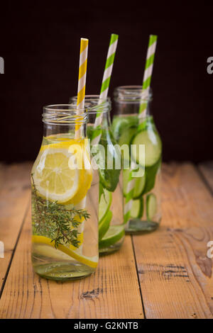 Three glass bottles of table water flavored with different fruits and herbs - Stock Photo