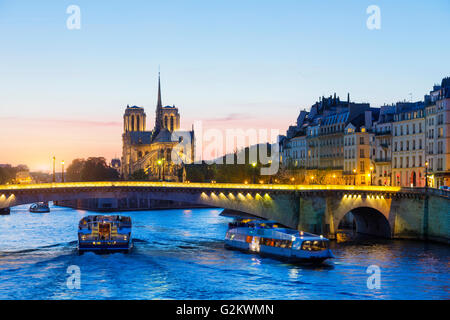 Paris, Tour boat on the Seine river at sunset with Notre Dame de Paris Cathedral in Background - Stock Photo