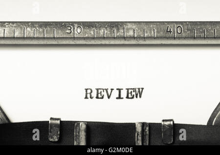 Word review typed on an old typewriter - Stock Photo