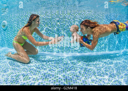 Child swimming lesson - baby with mother, father learn to swim, dive underwater in swimming pool. - Stock Photo