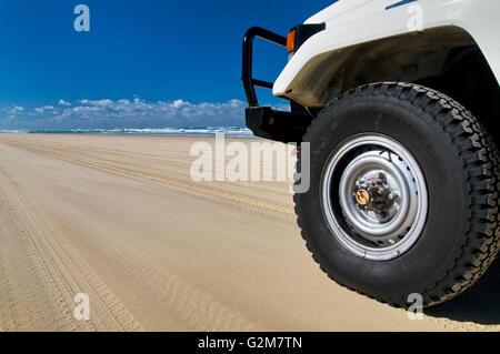 Car on Fraser Island's 75 Mile Beach. - Stock Photo