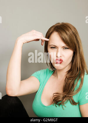 Portrait of a Young Woman Pulling Silly Funny Faces With Pouting Lips and Frowning Looking at the Camera - Stock Photo