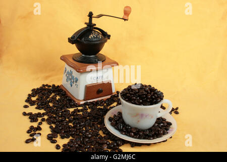 coffee cup full of cofee and a coffee grinder on yellow background - Stock Photo