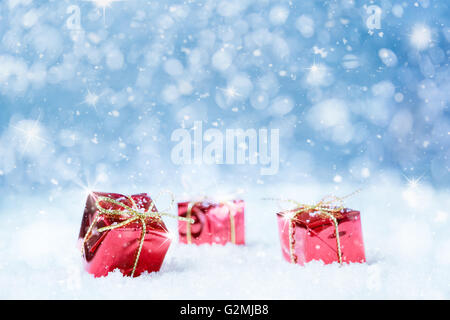 Red christmas presents with snow and stars on a blue background for a greeting card or voucher.Selected focus, narrow - Stock Photo