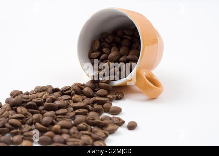 coffee beans pouring out from an orange coffee cup - Stock Photo