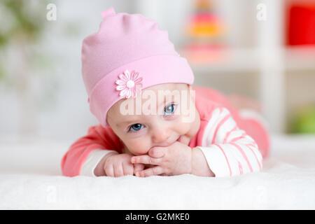 Baby teething sucks fingers. Infant kid lying in nursery - Stock Photo