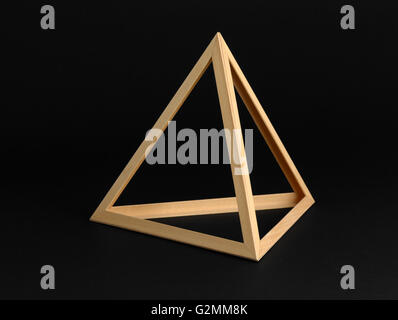Three dimensional geometric wooden triangular frame isolated on a black background - Stock Photo