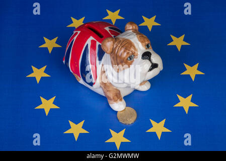 British bulldog sits in EU stars and keeps one paw on a pound coin - Stock Photo