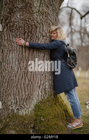 Beautiful blonde girl is hugging tree - Stock Photo