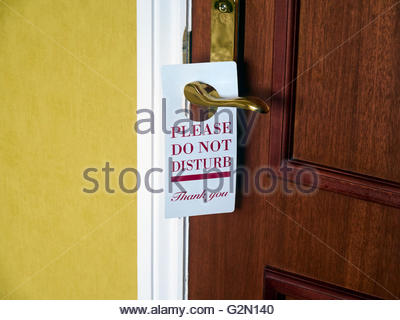 Please do not disturb sign hanging on a brass door handle in a hotel - Stock Photo