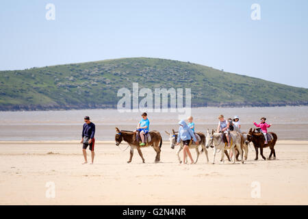 A group of children riding along a beach on seaside donkeys - Stock Photo