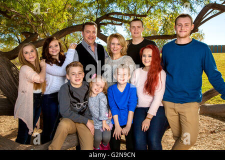 Portrait of a large family at the park, under a tree.  Parents with their eight children.  Three brothers and fours - Stock Photo