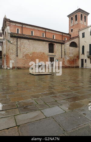 Church in Venice, Italy, on a rainy day, with a well in its courtyard - Stock Photo