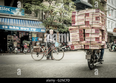 Vietnamese person pushing a traditional bike alongside a heavily ladened motorcyle in a typical street with traffic - Stock Photo