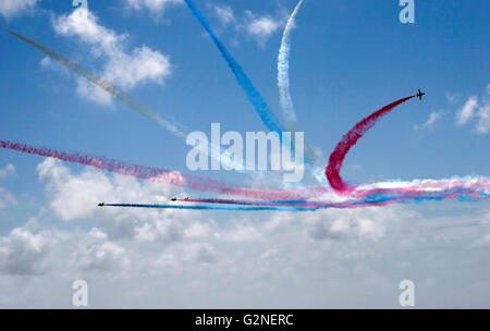 Red Arrows flying against a blue sky - Stock Photo