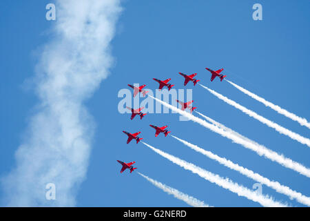The Red Arrows formation flying against a blue sky - Stock Photo