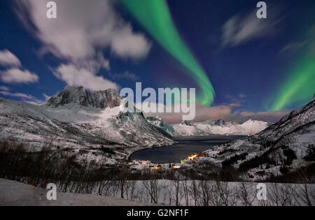 Aurora Borealis or northern lights over winter landscape in fjord of Mefjorden, Senja, Troms, Norway, Europe - Stock Photo