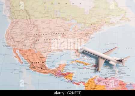 Miniature Of A Passenger Airplane Flying Over The Map Of United States Of America From South