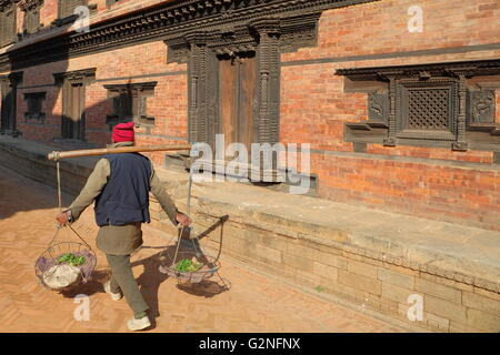 A local seller carrying vegetable in baskets at Durbar Square in Bhaktapur, Nepal - Stock Photo