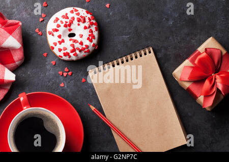 Donut, coffee and gift box on stone table. Top view with notepad for copy space - Stock Photo