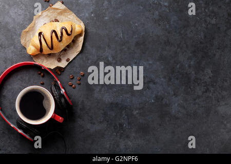 Fresh homemade croissant with chocolate and coffee on stone table. Top view with copy space - Stock Photo