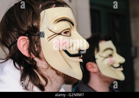 People wearing Guy Fawkes masks, synonymous with the hacker group 'Anonymous' . Belfast 11/02/2012 - Stock Photo