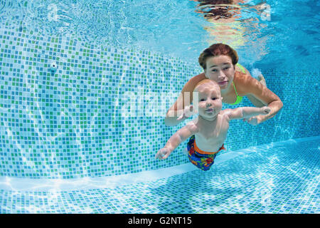 Child swimming lesson - baby with mother learn to swim, dive underwater in swimming pool. - Stock Photo