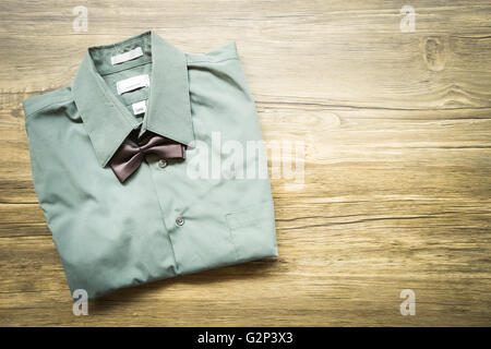 Top view Men's outfits with green shirt and tie on old wood table - Stock Photo