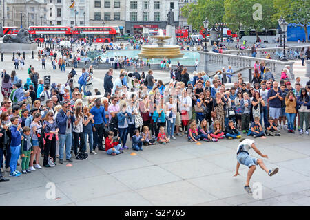 Large crowd of people including tourists gather around street performer gymnastic dancing in front of spectators - Stock Photo