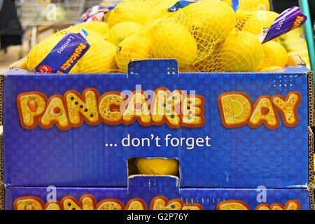 UK English supermarket food store shopping promotion display don't forget Pancake Day lemons sold in string bags - Stock Photo