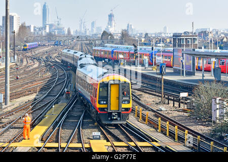 Urban landscape train tracks & distant London skyline with South West Trains passenger service returns to depot - Stock Photo
