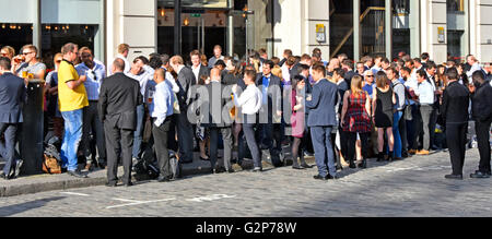 Predominately office workers standing talking chatting & drinking in the street outside bar restuarant premises - Stock Photo