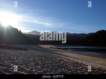 Sun setting across Abel Tasman - Stock Photo