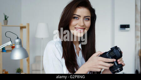 Side view of attractive smiling brunette female photographer in white shirt checking an image holding her camera, - Stock Photo