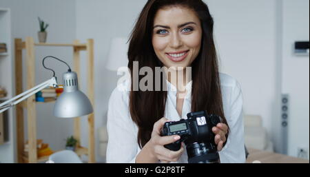 Attractive smiling brunette female photographer in white shirt checking an image holding her camera, office interior - Stock Photo